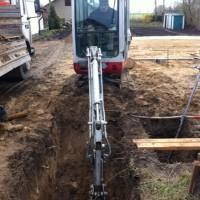 Bagger im Einsatz: Abwasser-Anschluss, Graben und Übergabeschacht