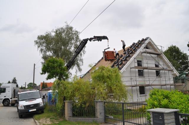Sattelschklepper samt Kran bringt die Dachziegel