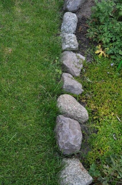 Steine als Beetbegrenzung des Rasens
