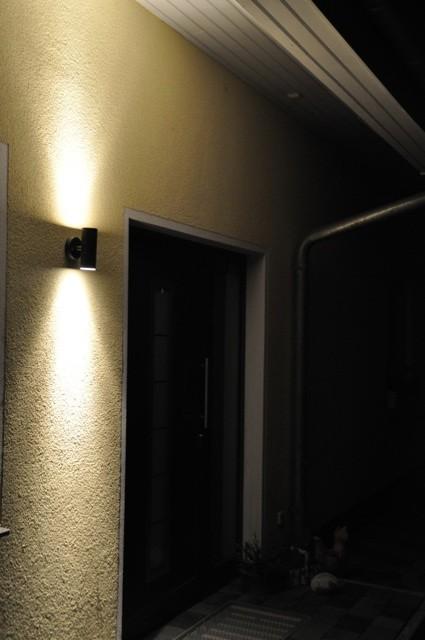 Wandlampe an der Fassade - Lichtstrahl scheint an der Hauswand nach oben und unten