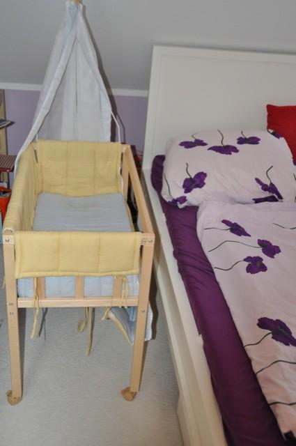 Babybett / Zustellbett auf Rollen neben dem Elternbett