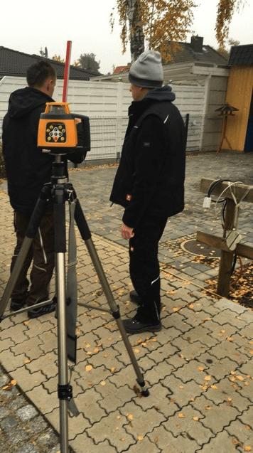 Vermessung neuer Zaun beim Hausbau - Gefälle wird gemessen