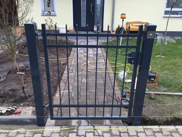 Eingangspforte des neuen Gartenzaun steht