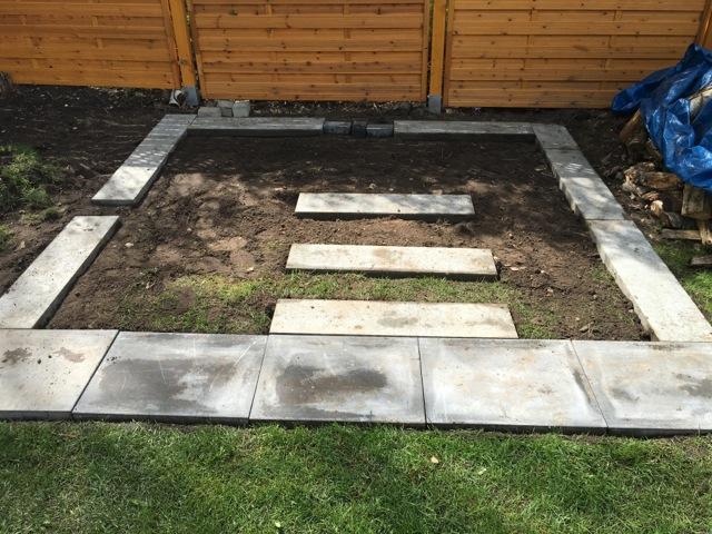 Fundament aus Terrassenplatten und Rasenkantsteinen als Unterbau für das Gartenhaus