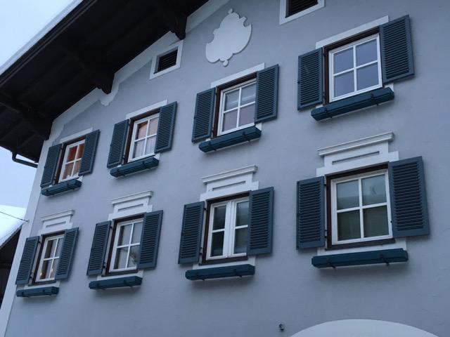 Hausansicht im Landhausstil mit Fensterläden