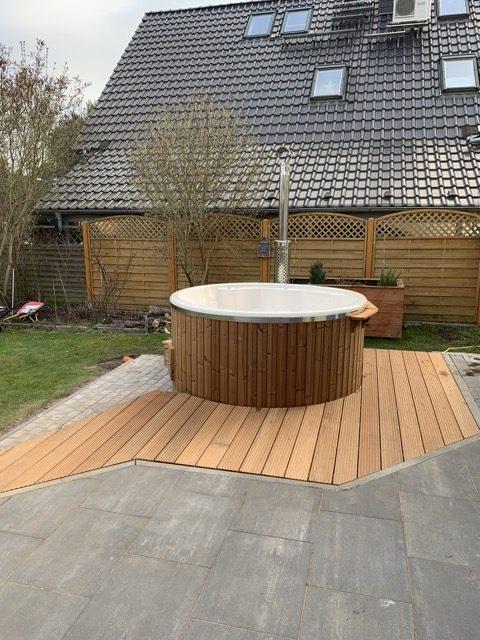 Badefass aus Holz mit Kunststoff und Ofen im Garten mit Anschluss an die Terrasse