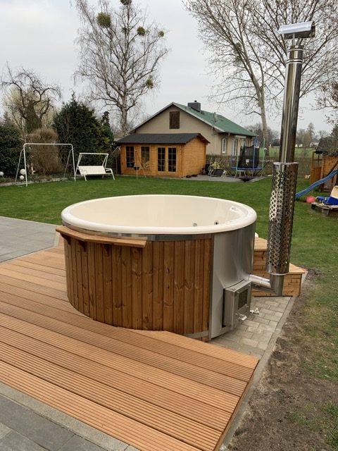 Badefass aus Holz nicht ganz bodentief in Terrasse eingelassen